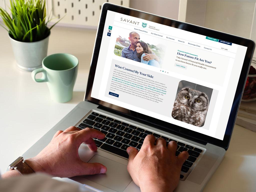 Laptop User Browsing Savant Wealth Management Website